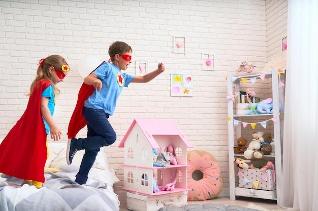Linda niña y niño saltando de la cama para volar