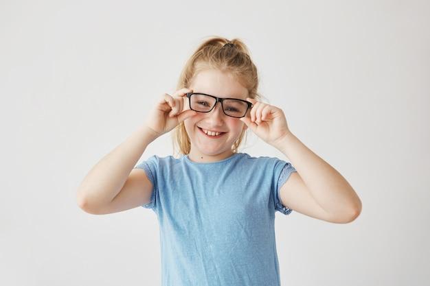 Linda niña con ojos azules y cabello claro sonrisas juega con mamá tomando sus lentes y probándose. felices momentos familiares.