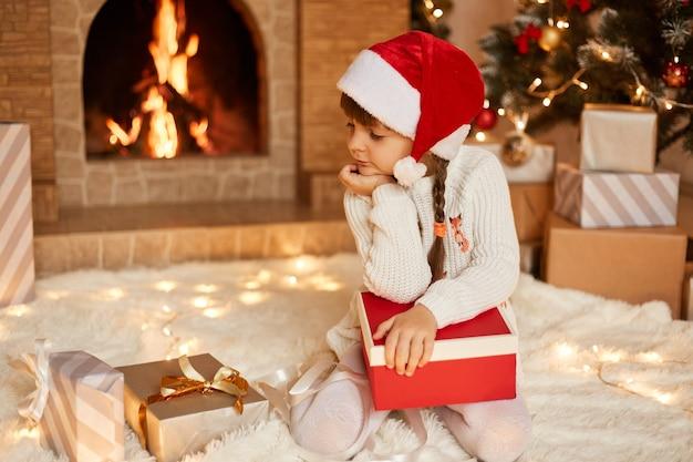 Linda niña pensativa vestida con suéter blanco y sombrero de santa claus, mirando las cajas actuales con expresión facial pensativa, posando en la sala festiva con chimenea y árbol de navidad.