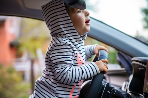Linda niña pequeña conduciendo un coche moderno.