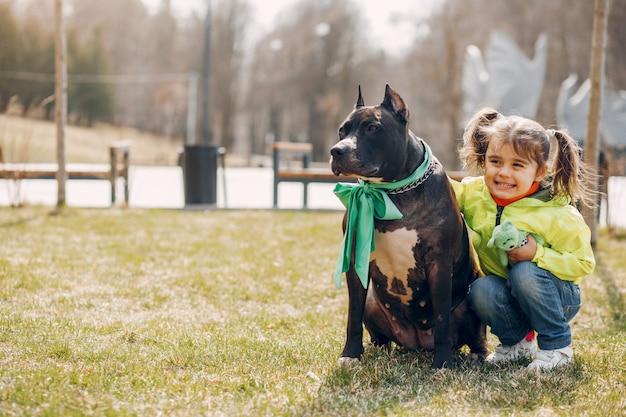 Linda niña pequeña en el parque con un perro