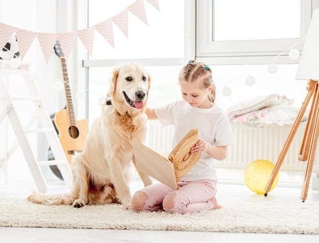 Linda niña y perro leyendo