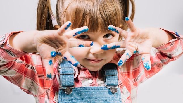 Linda niña de pie con los dedos pintados