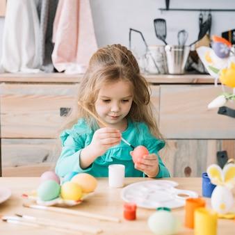Linda niña pintando huevos para pascua