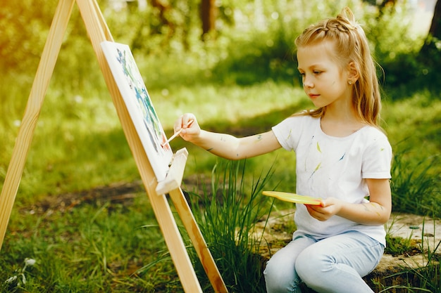 Linda niña pintando en un parque