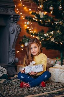 Linda niña con regalos junto al árbol de navidad.