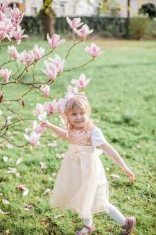 Linda niña rubia de 3 años juega en un parque cerca de una magnolia floreciente.