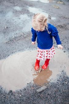 Linda niña rubia con botas de lluvia roja saltando en un charco