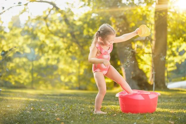 La linda niña rubia jugando con agua salpica en el campo en verano