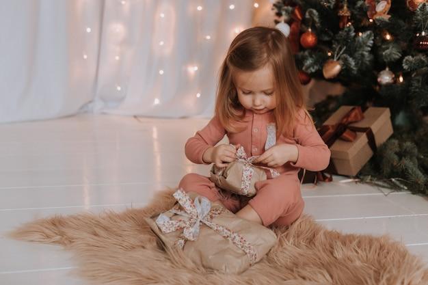 Linda niña rubia en pijama rosa abre regalos de navidad bajo el árbol de navidad
