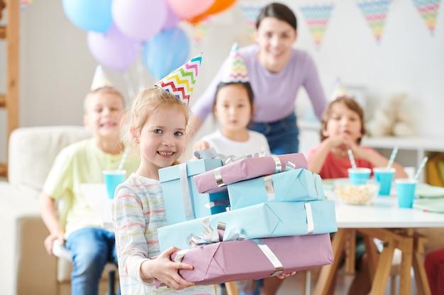 Linda niña rubia con regalos de cumpleaños de pie durante la fiesta en casa con amigos