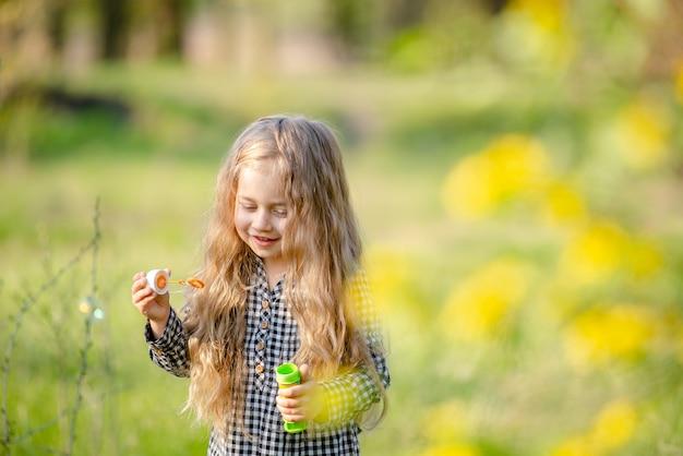Linda niña rubia soplando pompas de jabón divirtiéndose en el parque de la primavera.