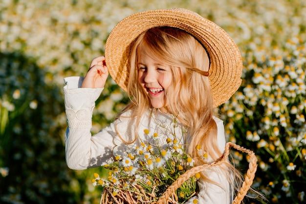 Linda niña rubia con un vestido de algodón y sombrero de paja camina en un campo de margaritas las recoge en la canasta
