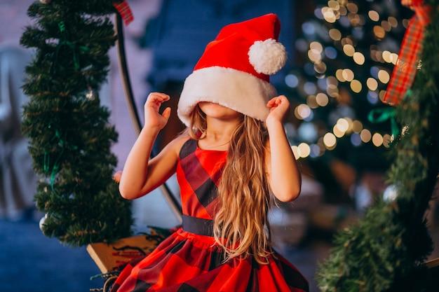 Linda niña en santa sombrero y vestido rojo