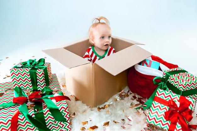 Linda niña sentada en caja sobre fondo de navidad. vacaciones, celebración, concepto de niño