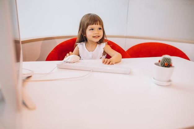 Linda niña sentada a la mesa en una sala de exposición de automóviles