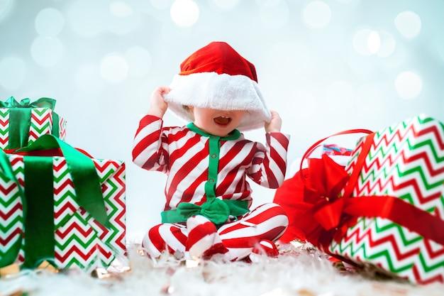 Linda niña con sombrero de santa posando sobre adornos navideños con regalos. sentado en el suelo con bola de navidad. temporada de vacaciones.