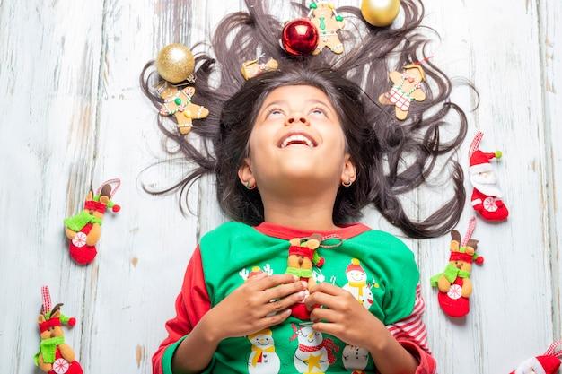 Linda niña sonriente alegre con el pelo decorado de navidad