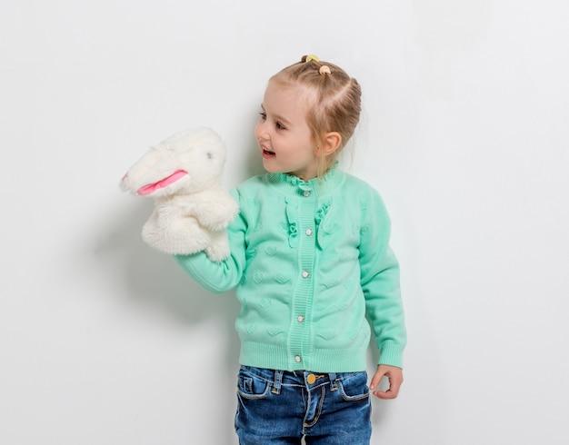 Linda niña sonriente jugando liebre de juguete