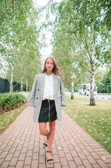 Linda niña sonriente posando delante de su escuela