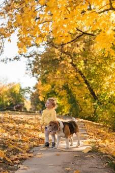 Linda niña sonriente y su perro mascota de pie en la pasarela del parque
