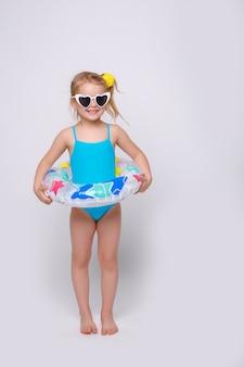 Linda niña sonriente en traje de baño con anillo de goma aislado en blanco