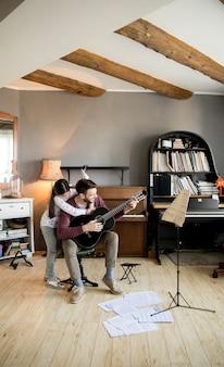 Linda niña y su apuesto padre están tocando la guitarra