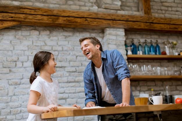Linda niña y su guapo padre preparando pasta en la cocina