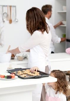 Linda niña tomando galletas mientras sus padres están cocinando