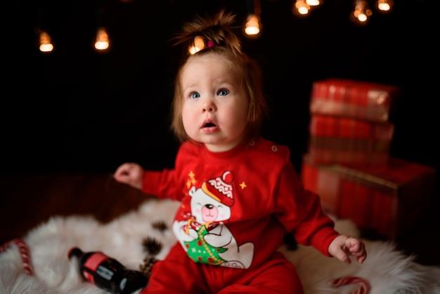 Linda niña en un traje rojo de navidad con guirnaldas retro se sienta sobre una piel