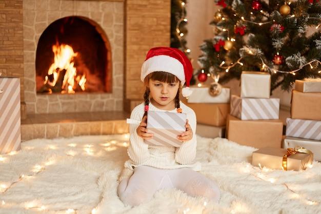 Linda niña vestida con suéter blanco y sombrero de santa claus, posando en la sala festiva con chimenea y árbol de navidad, sosteniendo la caja de regalo en las manos, mirando al presente con asombro.
