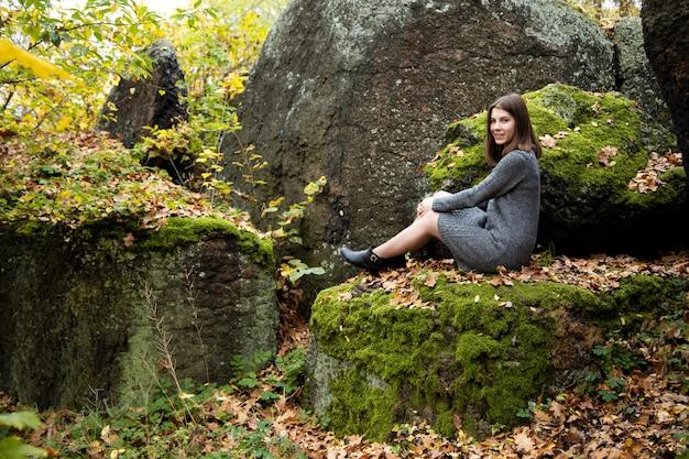 Una linda niña con un vestido gris se sienta en el otoño en una piedra cubierta de musgo en el bosque y sonríe agradablemente.