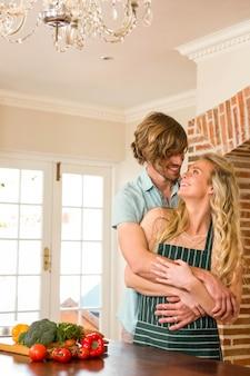 Linda pareja abrazándose con los brazos alrededor en la cocina