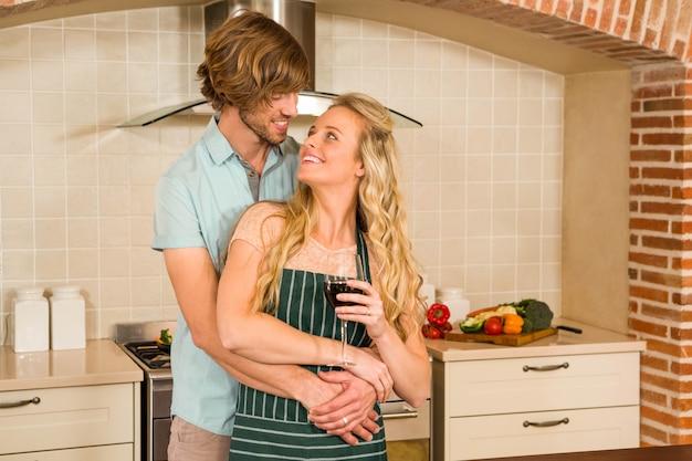 Linda pareja abrazándose y disfrutando de una copa de vino en la cocina