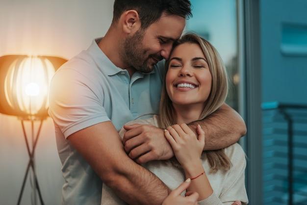 Linda pareja abrazándose y sonriendo en su nuevo hogar.