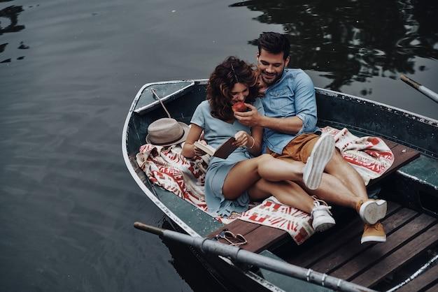 Linda pareja. apuesto joven alimentando a su novia con una manzana mientras está sentado en el barco