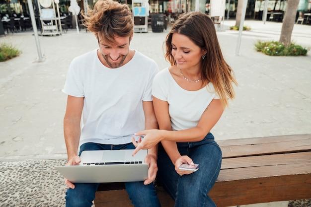 Linda pareja en un banco con laptop
