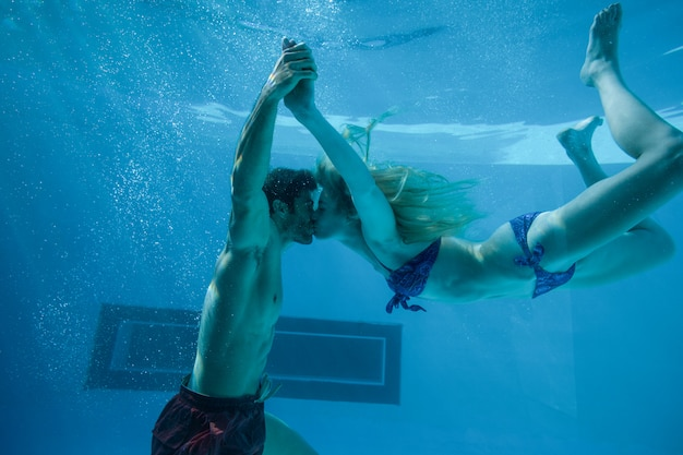 Linda pareja besándose bajo el agua en la piscina
