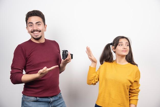 Linda pareja con cámara posando sobre una pared blanca.