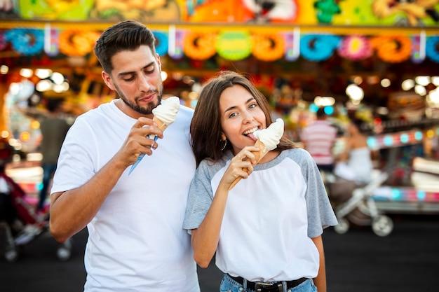 Linda pareja comiendo helados en la feria