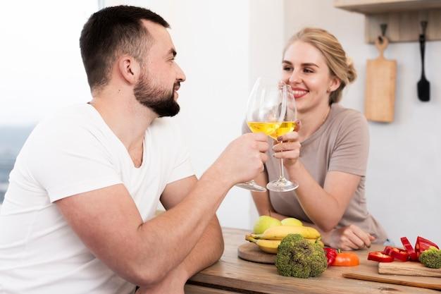 Linda pareja comiendo verduras y bebiendo juntos