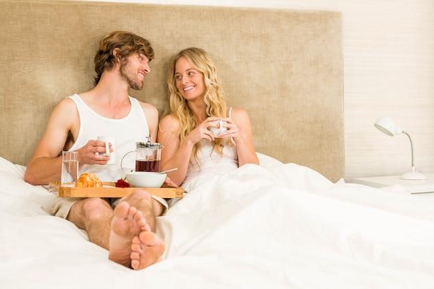 Linda pareja desayunando en la cama en el dormitorio.