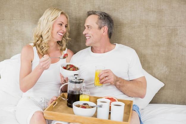 Linda pareja desayunando en la cama en su habitación.