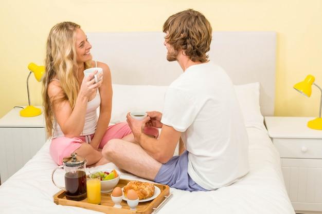 Linda pareja desayunando sentada en su cama en el dormitorio