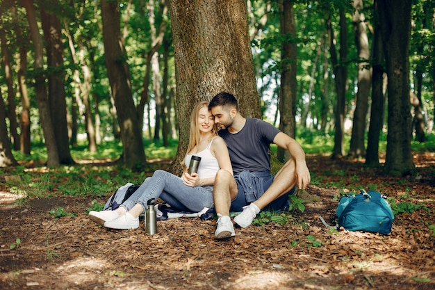 Linda pareja descansa en un bosque de verano
