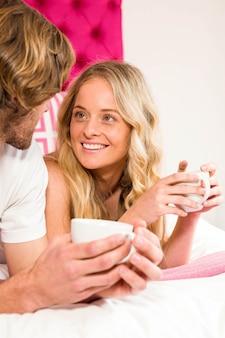 Linda pareja descansando en su cama y tomando un café en su habitación
