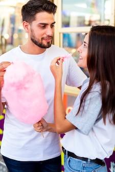Linda pareja disfrutando de algodón de azúcar