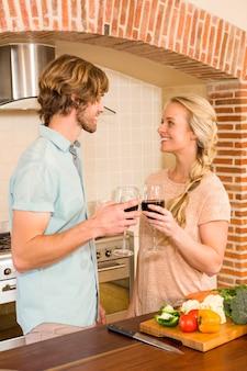 Linda pareja disfrutando de una copa de vino en la cocina