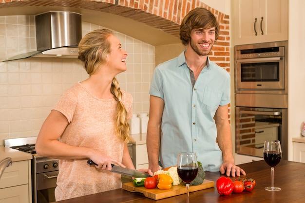 Linda pareja disfrutando de una copa de vino y rebanar verduras en la cocina