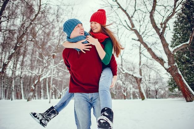 Linda pareja divertirse en un parque de invierno
